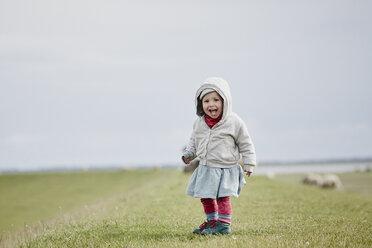 Germany, Schleswig-Holstein, Eiderstedt, happy little girl standing on dyke - RORF00742