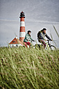 Germany, Schleswig-Holstein, Eiderstedt, couple riding bicycle near Westerheversand Lighthouse - RORF00745