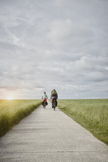 Germany, Schleswig-Holstein, Eiderstedt, couple riding bicycle on path through salt marsh - RORF00748