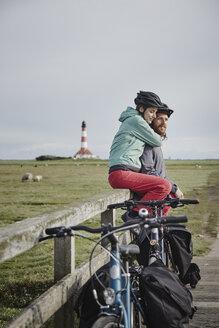 Germany, Schleswig-Holstein, Eiderstedt, couple on bicycle trip having a break near Westerheversand Lighthouse - RORF00751