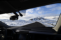 Iceland, road and snow-capped mountain seen from inside car - RAEF01785