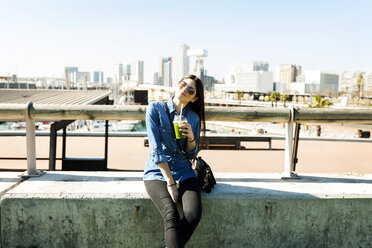 Spain, Barcelona, smiling young woman with beverage enjoying sunlight - VABF01271