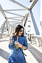 Spain, Barcelona, laughing young woman with beverage on a bridge - VABF01274