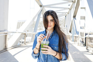 Spain, Barcelona, portrait of smiling young woman with beverage on a bridge - VABF01277