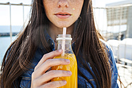 Young woman with bottle of orange juice, partial view - VABF01280