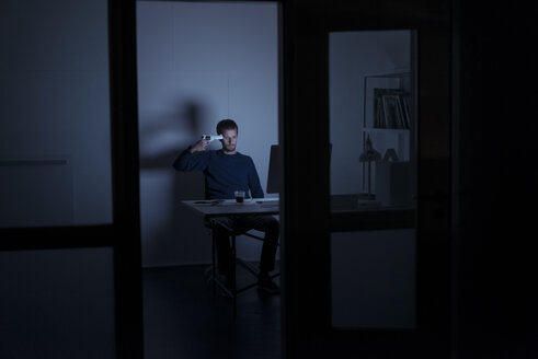 Man working late in office holding gun at his head - KNSF01192