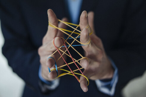 Close-up of businessman holding rubber bands - KNSF01204