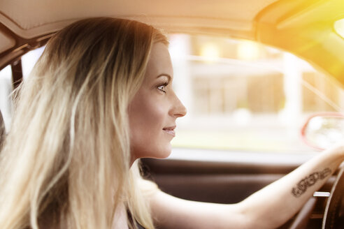 Smiling blond woman driving car - DMOF00005