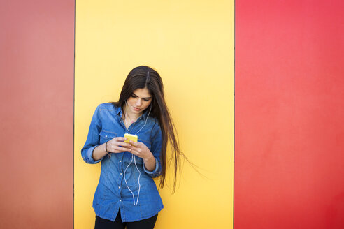 Young woman with earphones and smartphone standing in front of colourful wall - VABF01287
