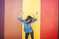 Happy young woman dancing in front of colourful wall - VABF01290