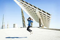 Young woman jumping in the air with solar panels in background - VABF01293