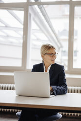 Businesswoman using laptop in office - JOSF00702