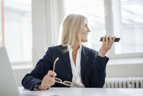 Businesswoman using cell phone in office - JOSF00705