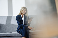 Smiling businesswoman sitting on couch holding tablet - JOSF00708