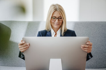 Businesswoman looking at computer screen in office - JOSF00711