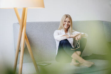 Portrait of smiling relaxed businesswoman sitting on couch - JOSF00714