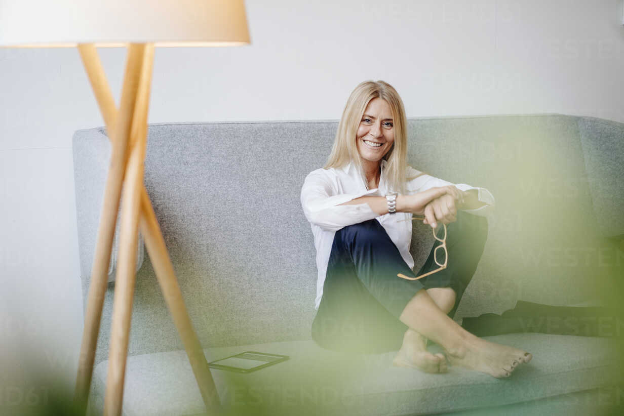 Portrait of smiling relaxed businesswoman sitting on couch - JOSF00714 - Joseffson/Westend61