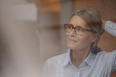 Businesswoman behind rainy windowpane looking away - JOSF00726