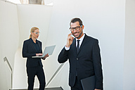 Smiling businessman on cell phone and businesswoman using laptop outdoors - CHAF01831