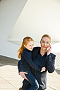 Businesswoman on the phone holding daughter - CHAF01837