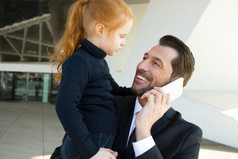Smiling businessman on the phone holding daughter - CHAF01840