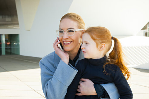 Smiling businesswoman on the phone hugging daughter - CHAF01843