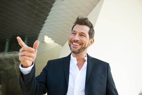 Portrait of confident businessman outdoors pointing his finger - CHAF01846