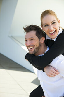 Portrait of happy businessman carrying woman piggyback - CHAF01855