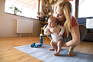 Smiling mother with baby and dumbbells at home - HAPF01368