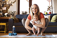 Smiling mother with baby and dumbbells at home - HAPF01371