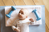 Baby at home lying on mat next to dumbbells - HAPF01374