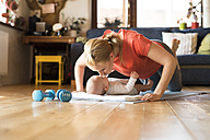 Happy mother kissing baby at home lying on mat next to dumbbells - HAPF01377