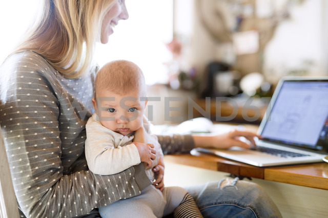 Mother with baby at home using laptop - HAPF01389