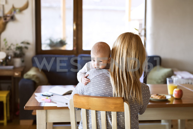 Mother with baby at home sitting at table - HAPF01392