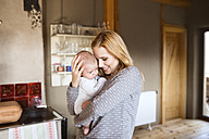 Smiling mother holding baby at home - HAPF01398