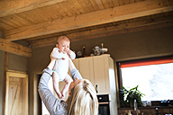 Mother lifting up baby at home - HAPF01401