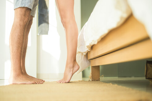 Low section of couple standing in bedroom - SIPF01537