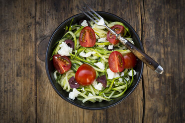 Bowl of zucchini spaghetti with feta, cherry tomatoes and black olives on wood - LVF05983