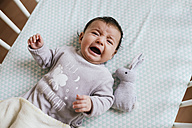 Portrait of crying baby girl lying in crib with toy bunny - GEMF01555