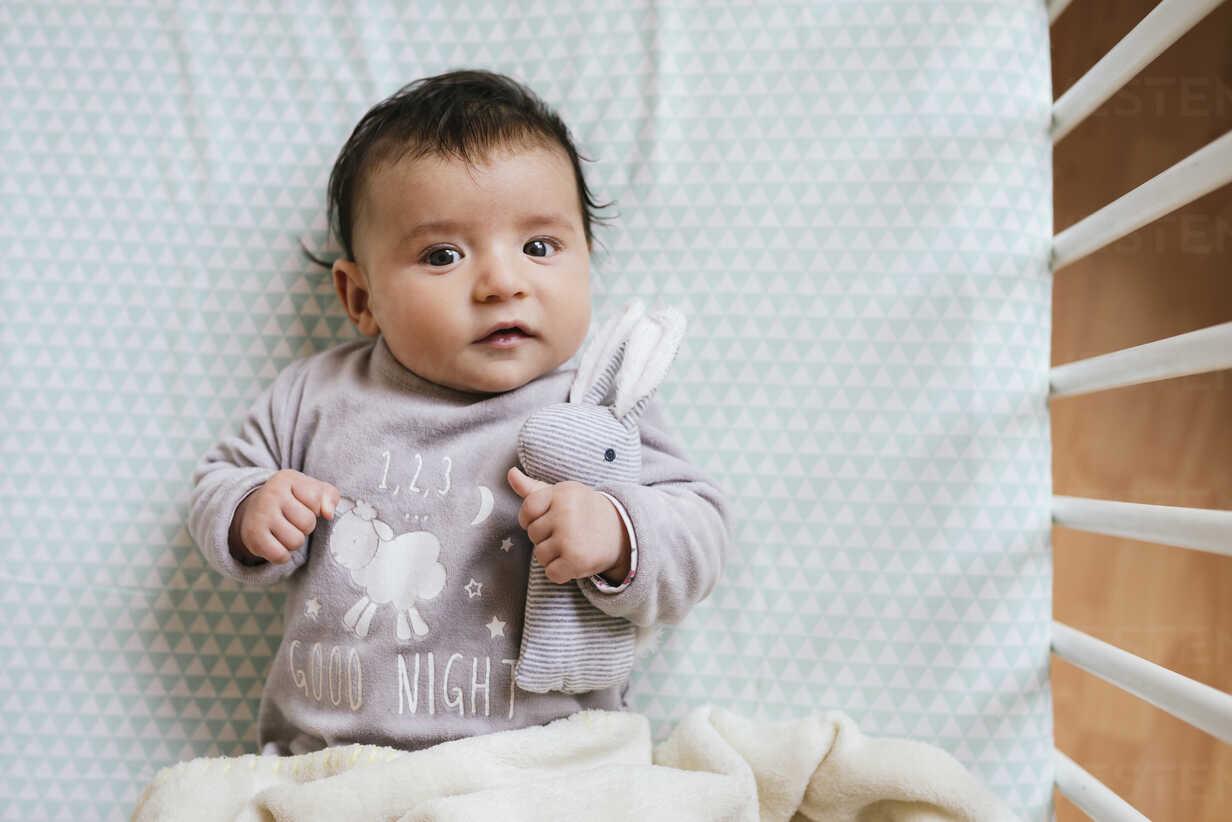 Portrait of baby girl lying in crib with toy bunny - GEMF01558 - Gemma Ferrando/Westend61