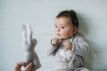 Baby girl lying on crib looking at hand holding toy bunny - GEMF01564
