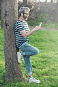 Bearded man leaning against tree trunk looking at smartphone - RTBF00790