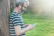 Bearded man leaning against tree trunk looking at smartphone - RTBF00793