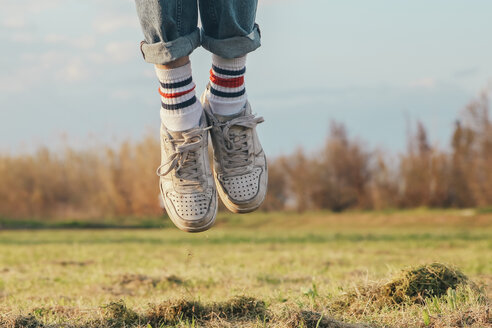 Shoes of man jumping on meadow - RTBF00799