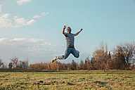 Smiling man jumping in the air while taking photo with vintage camera - RTBF00802