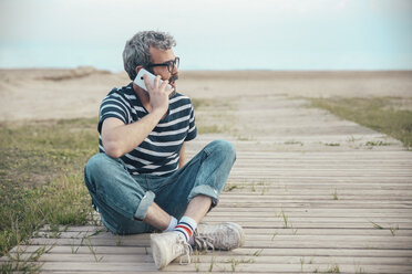 Man on the phone sitting on boardwalk looking at distance - RTBF00805