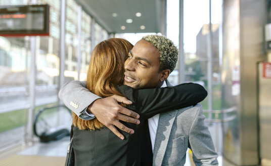 Young businessman and woman embracing at metro station - DAPF00611