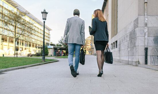 Young businessman and woman walking in the city - DAPF00614