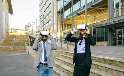 Young businessman and woman using VR goggles - DAPF00638