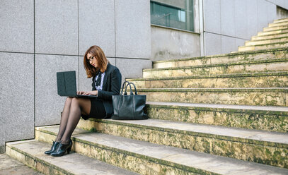 Businesswoman sitting on stairs, using laptop - DAPF00641